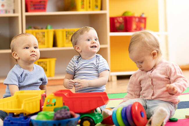 Three happy children playing with toys in a bright and cheerful childcare classroom.