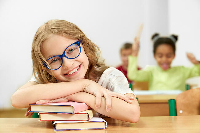 Close up of a happy student sitting at a desk.