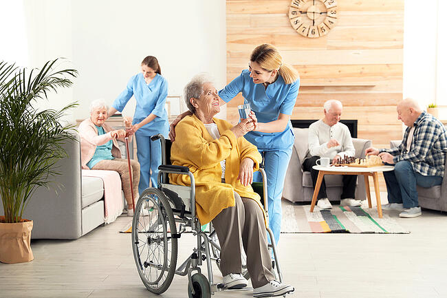 A medical assistant helping a patient in a wheelchair.
