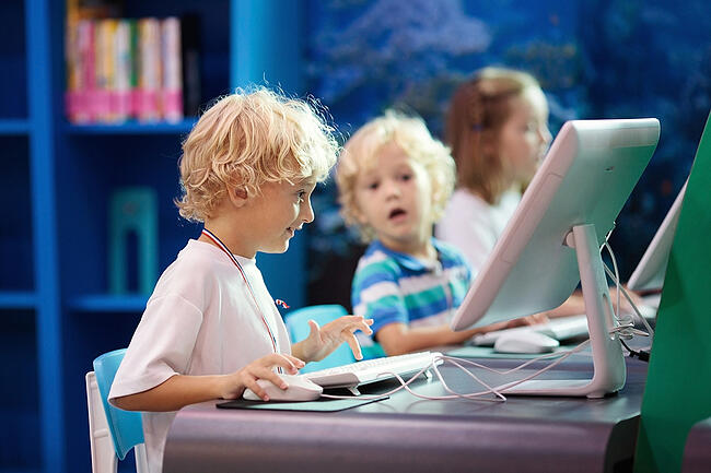 Young children in a classroom on computers.