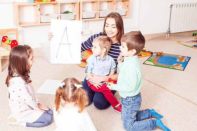 Young preschool teacher with a group of small children in a classroom.