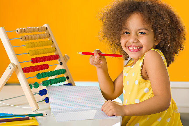Young student smiling and holding a pencil.