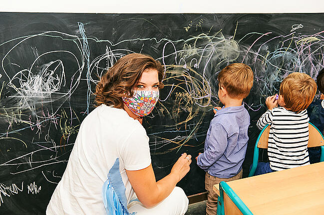 New teacher drawing on a chalkboard with young students.