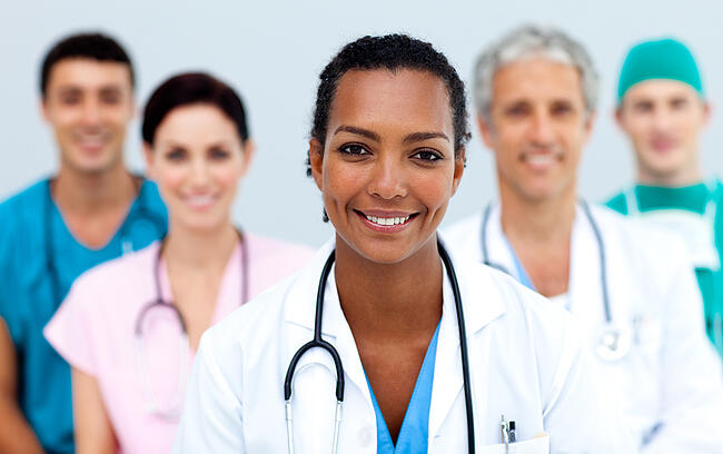 Female doctor with medical staff behind her all smiling at the camera.