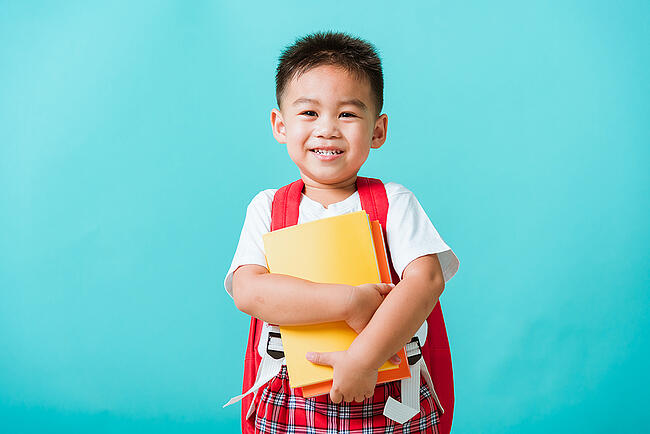 Preschool student wearing a backpack and holding books.