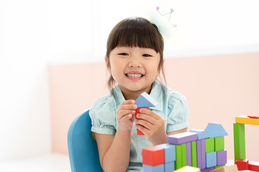 Young child playing with blocks in a classroom.