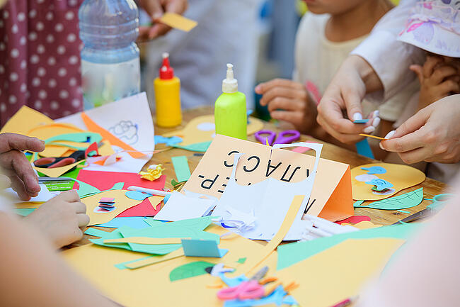 Young students working on an art project with construction paper and glue.