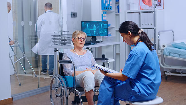 Medical assistant sitting with an elderly patient in a healthcare facility.