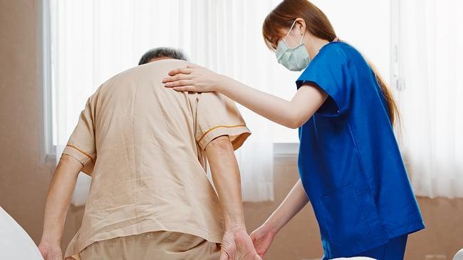 Medical assistant helping an elderly man.