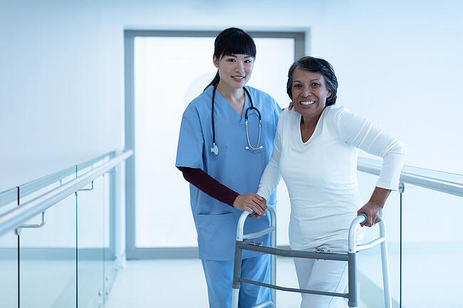 Medical assistant helping a patient walk with a walker in a hospital setting.