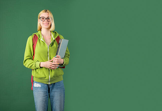 Smiling college student wearing a backpack and holding books.