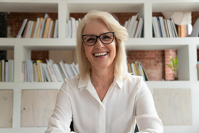 Mature teacher smiling at her desk in front of a bookshelf.