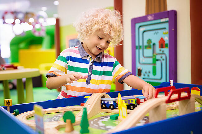 Young smiling child playing with toys in a preschool classroom.