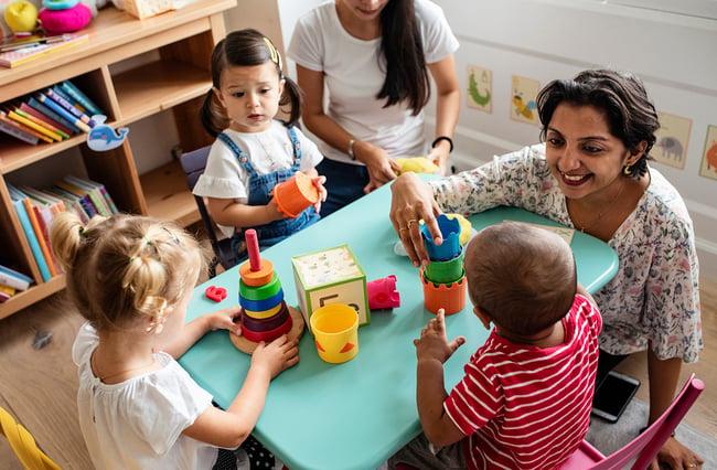 Smiling preschool teacher interacting with young children.
