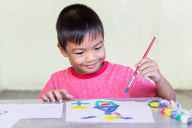 Young student painting with watercolors and a paintbrush on white paper.