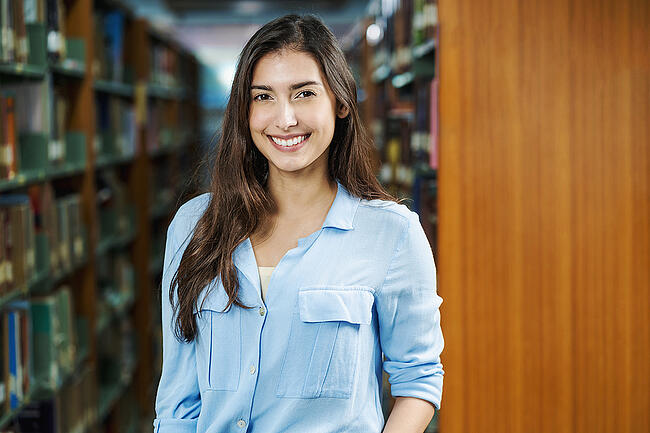 Smiling college student standing in a library.