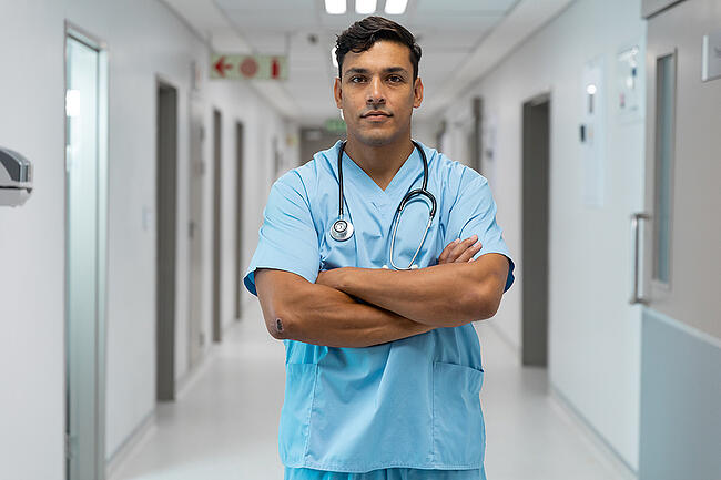 Medical assistant standing in a hospital hallway.