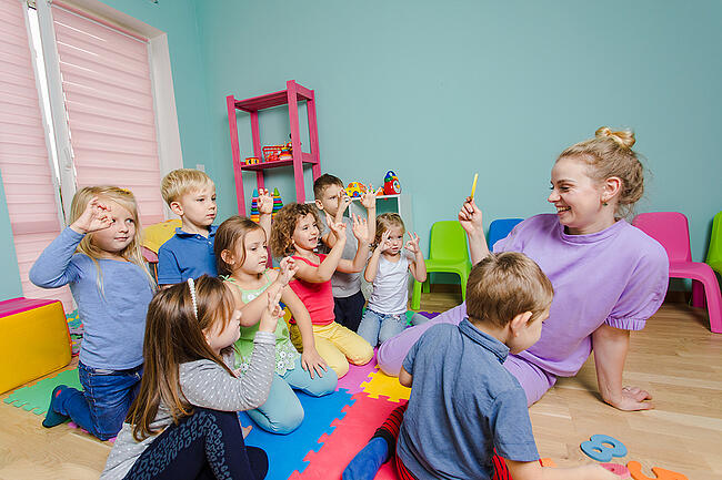 Preschool teaching interacting with young students.