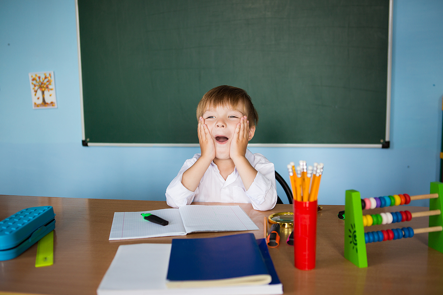 Small student sitting at the teacher's desk.