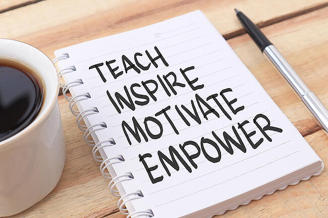 Note pad with words TEACH INSPIRE MOTIVATE EMPOWER written in black marker.