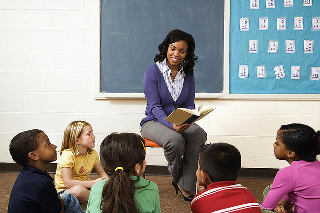 Teacher reading to a group of young students in a classroom.