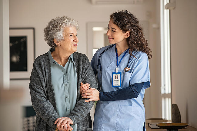Smiling medical assistant helping a long term care resident.