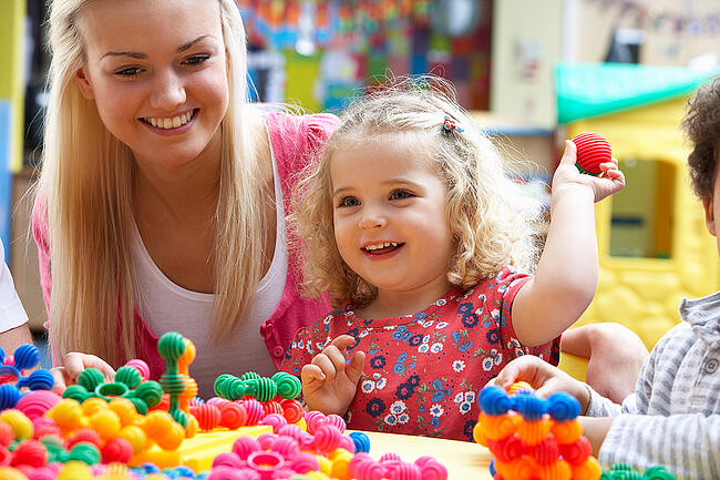 Young blonde preschool teaching working with a little girl in a classroom.