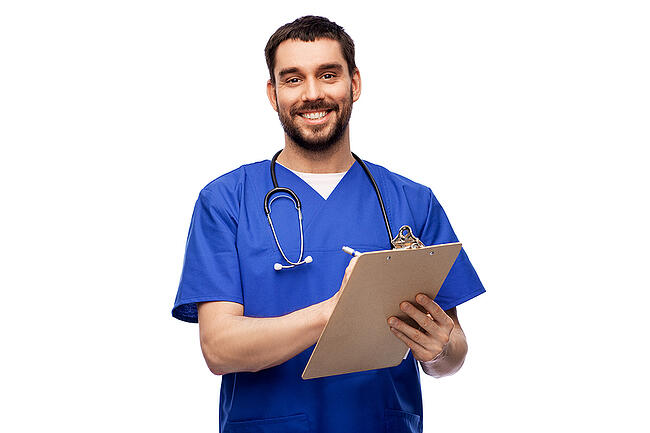 Smiling male medical assistant holding a clipboard and a pen.
