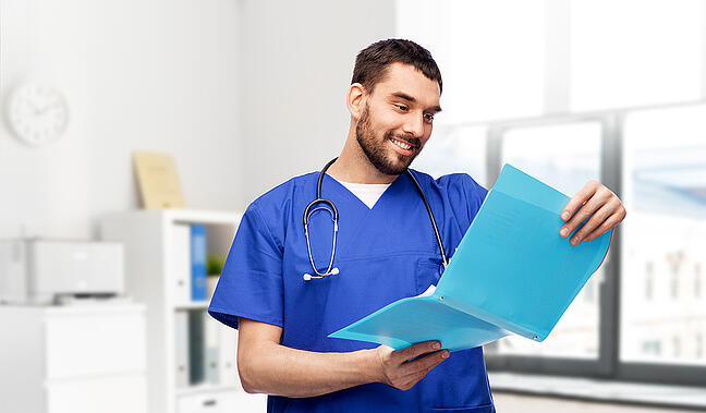 Male medical assistant looking at a patient file before an appointment.