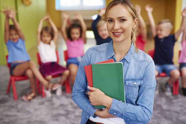 Preschool teacher in front of a classroom full of kids sitting in chairs.