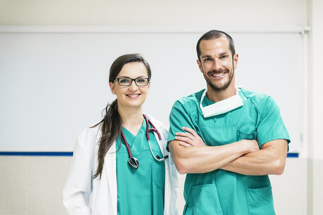Two medical assistants wearing scrubs.